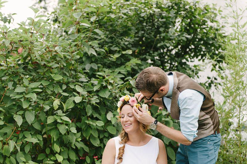 marié remet une fleur dans la couronne de fleurs de la mariée