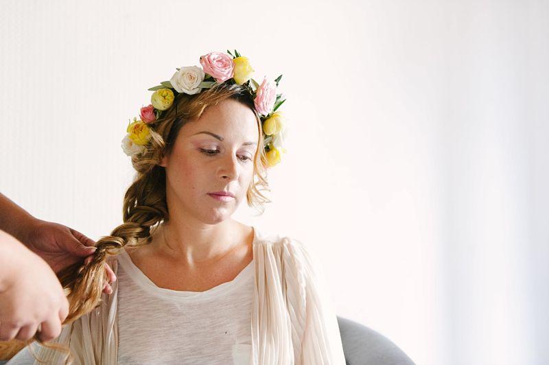 mariée se faisant coiffer tresse et couronne de fleurs