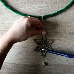 étoile en bois et grelot fixé à un cercle en métal