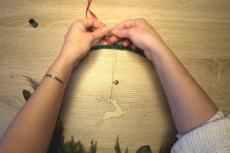cerf en bois attaché à une couronne de noël