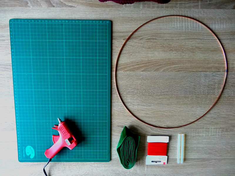 plan de travail, pistolet à colle, ruban rouge et vert, colle, cercle métal
